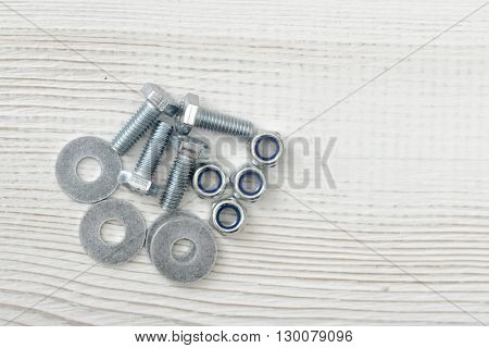 Layout with nuts, bolts and washers distributed on wooden surface with copy space. Top view of construction tools. Mend and repair. Parts for repair. Fixing stuff.
