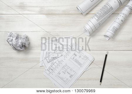 Torn and crumpled sketches lie on a wooden surface. Top view compositin. Workplace of architect or constructor. Engineering work. Failure. Construction and architecture. Architect drawing. Exact calculation. Anger sign.