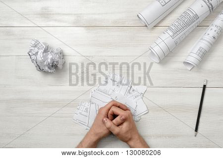 Close-up masculine folded hands on wooden panel with hand-folding a piece of paper. Worry process. Top view composition. Anger sign. Workplace of architect or constructor. Engineering work. Construction and architecture. Architect drawing. Draft.