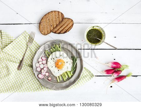 Healthy breakfast set. Fried egg with green asparagus, radishes, green sauce and bread on vintage metal plate over white wooden backdrop, top view