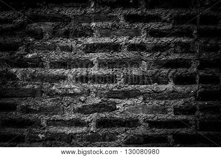 Rustic bricks and cement texture wall in darkened b&w theme and high vignette for background use