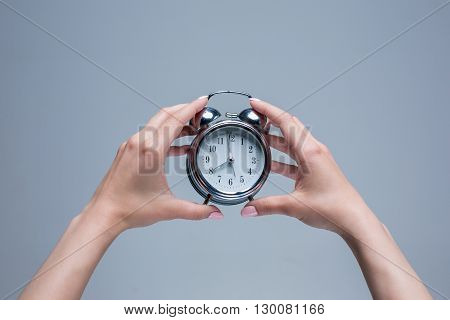 The female hands and old style alarm clock on gray background