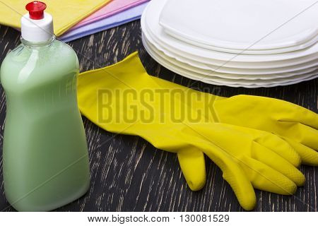 Detergent, rags dishes and latex gloves on wooden background