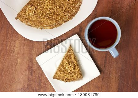 A cup of tea and a piece of cake on a plate next to the cake from which this slice has been cut shot from above on a dark wooden texture with copyspace