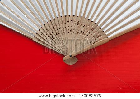 Typical Japanese hand fan made on the wooden red table