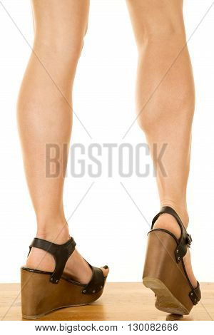 A woman's heels in he fancy wedge shoes on a wooden floor.