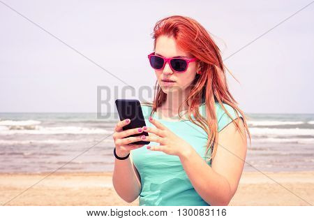 Young sad woman looking mobile phone on the beach - Girl unhappy facial expression reading message on smartphone outdoors - Concept of human bad feelings and internet communication - vintage filter