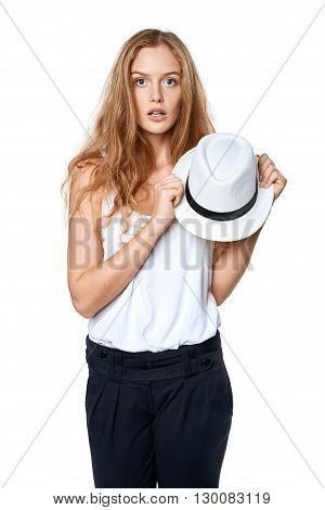 Surprised woman holding straw hat looking at camera