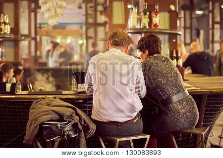 KYIV, UKRAINE - MAY 15, 2016: Middle-aged couple met to drink and talk at the bar of popular Street Food Festival on May 15, 2016. Kiev is the 8th most populous city in Europe.
