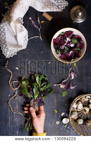 Girl's hand holding a bunch of herbs. Spring salad ingredients and eggs. Natural and healthy diet background. Top view.