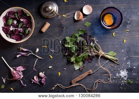 Spring radicchio salad with basil, garlic and yolk. Healthy food ingredients over wooden table. Overhead view.