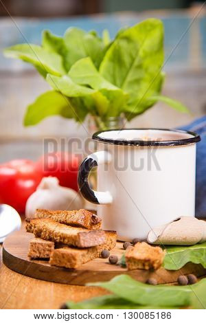 fresh hot soup and cracker in white cup with green sorrel in studio