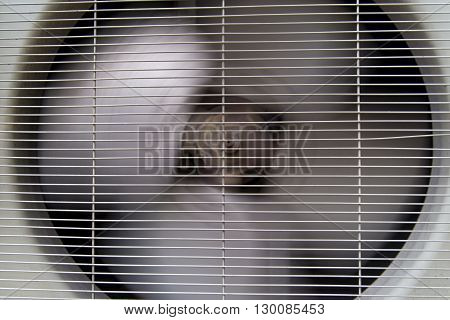 Close-up detail of the spinning fan of an air conditioner condenser