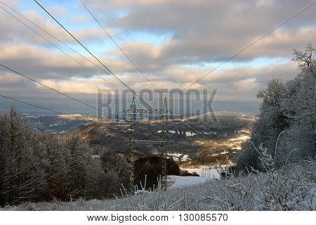 Electric posts in snow mountains in north Bohemia