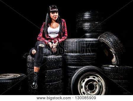 Young Woman In A Red Checked Shirt Sitting On A Tires