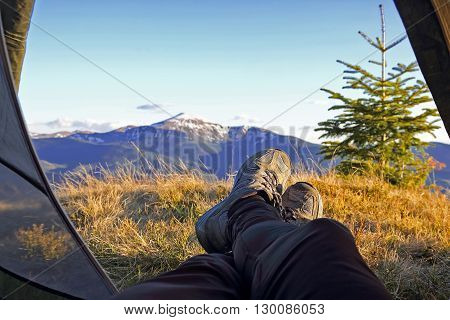 legs vacationer camper in tent with mountain view