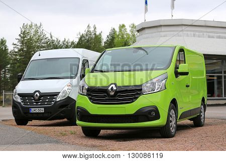 RAASEPORI, FINLAND - MAY 15, 2016: Lime green Renault Trafic DCi 140 and White Renault Master van parked on a yard.