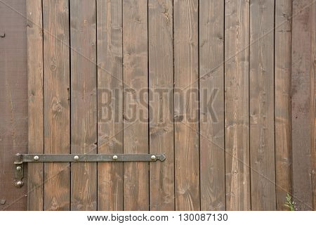 Hinge and part of brown wooden barn gate