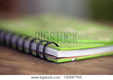 Green exercise book on table with white dogs pictures