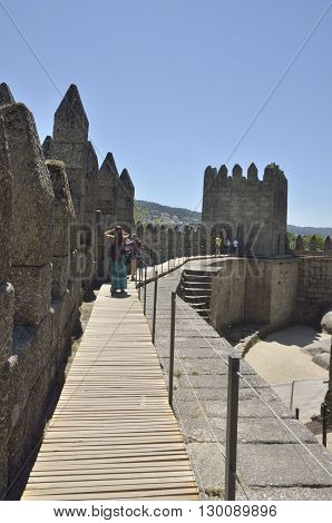 GUIMARAES, PORTUGAL - AUGUST 9, 2016: People at the top of the Castle of Guimaraes in the northern region of Portugal. It was built at the end of the 13th century following French influences.