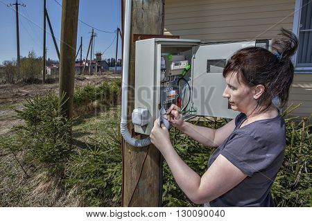 Rural adult women to take readings of electricity meter outdoors.