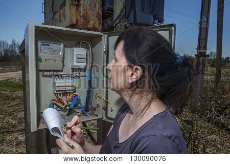 Woman Technician reading the electricity meter to check consumption standing near electricity switchgear power transformer substation outdoors.