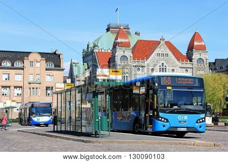 HELSINKI, FINLAND - MAY 12, 2016: Blue VDL city bus waits for passengers at Central Railway Station Square bus stop with the Finnish National Theatre on the background on a sunny spring day in Helsinki.