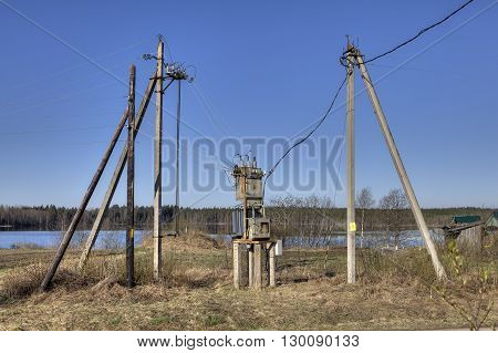 Electricity distribution transformer electrical power substation in the countryside spring sunny morning.
