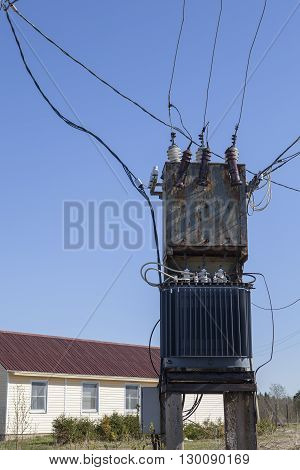 Electrical Power Distribution Transformer near the residential village house.