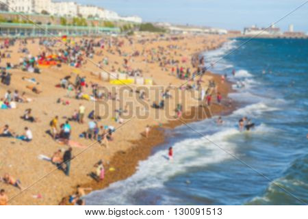 Blurred background of a beach with people sunbathing. Aerial view of the coastline with water and waves on the right. Photo taken in Brighton England.