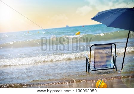 Beach Chair And Umbrella On The Water On The Beach