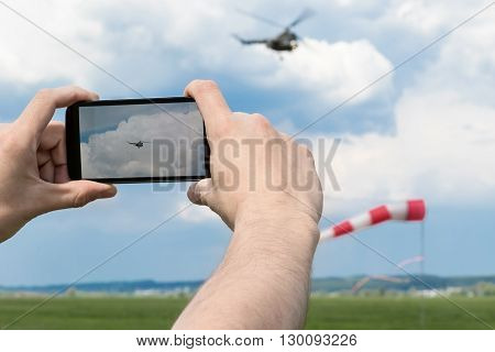 Male hands holding smartphone and photographed the helicopter in the blue sky