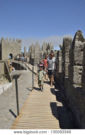 GUIMARAES, PORTUGAL - AUGUST 9, 2016: People in a path at the top of the Castle of Guimaraes in the northern region of Portugal. It was built at the end of the 13th century following French influences.