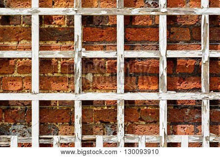 White wooden grate against red brick old weathered wall