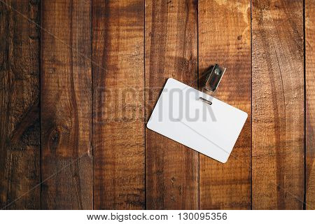 Blank badge on vintage wooden background. Blank plastic id card. Blank white plastic badge. Top view.