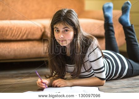 Schoolgirl doing lessons lying on the floor of the house.