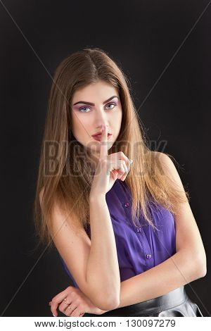 young beautiful woman shows gesture - quietly. a vertical portrait on a black background