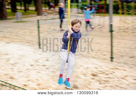 The boy is sliding down a rope on the playground