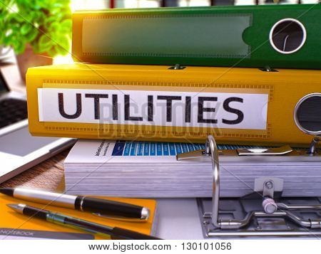 Utilities - Yellow Office Folder on Background of Working Table with Stationery and Laptop. Utilities Business Concept on Blurred Background. Utilities Toned Image. 3D.