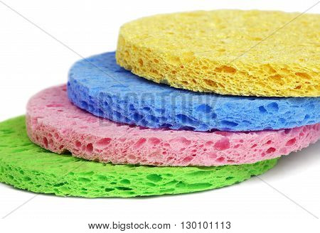 Some colorful round facial cleansing sponges isolated on white background.