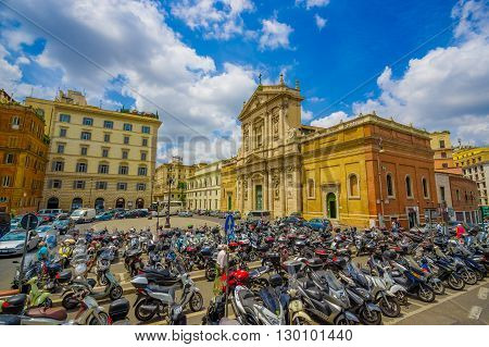 ROME, ITALY - JUNE 13, 2015: Nice church in the center of Rome city, outside motorcycle parking place. Cars crossing and turists visiting
