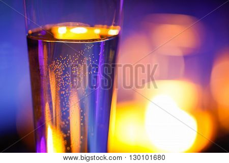 Close-up of candlelit glass with sparkling champagne. Love celebration relax romance luxurious vacation wellness spa concept.