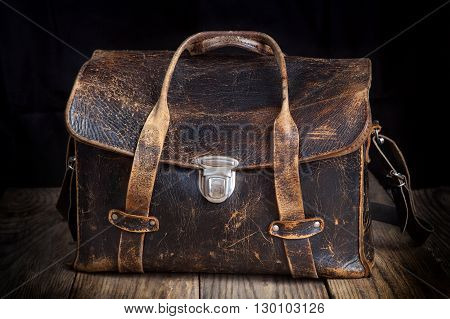 Old leather bag on wooden background, vintage style
