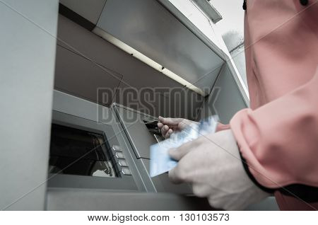 Man standing in front of an ATM machine withdrawing money holding a stash of credit and debit cards. 24/7 banking automated banking money fraud debt and financial crisis concept.