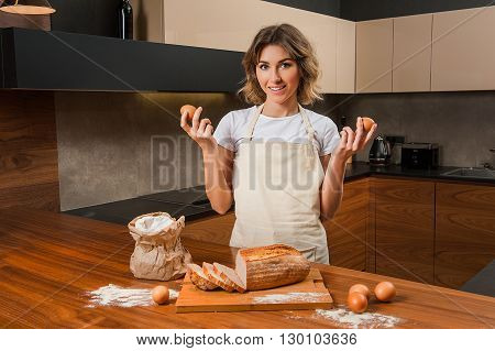 Portrait of a beautiful young lady in the kitchen holding eggs in her hands