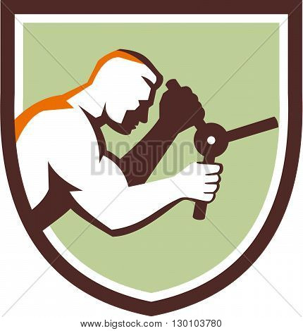 Illustration of a male worker opening safe handle viewed from side set inside shield crest done in retro style.