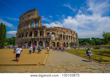 ROME, ITALY - JUNE 13, 2015: Roman coliseum view from outside, turists walking and visiting this iconic structure, summer day.