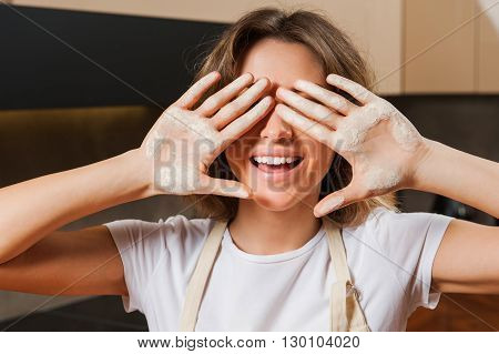 beautiful young lady  hiding her face behind hands dirty with flour