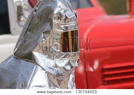 Fireman in special heat resistant suit on a background of fire engine