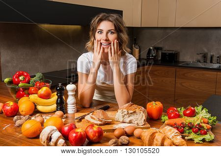 beautiful young lady  in the kitchen near the table with food